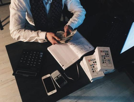 Person counting money at desk